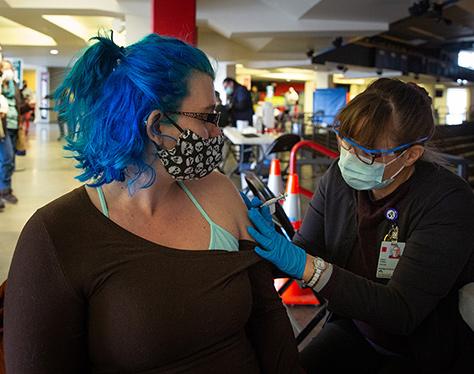 """Mujer recibiendo la vacuna Covid-19 en """"el pozo""""."""